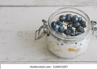 Overnight oats with fresh blueberry on wooden table, copy space. Easy oatmeal recipe for breakfast