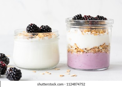 Overnight oats or healthy breakfast parfait with yogurt, granola and berries in jar on white background. Healthy eating, healthy lifestyle concept