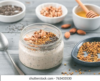 Overnight oats in jar and ingredients - chia seeds, almond, honey and pollen on gray wooden table background. Healthy breakfast oatmeal recipe idea