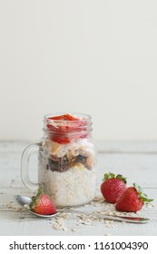 Overnight oats in a jar with strawberry on wooden table, vertical photo. Healthy breakfast recipe with fruits, whole grain and milk