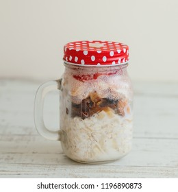 Overnight oats with milk, dried fruits, berries and nuts in a tall glass jar served on wooden table, square photo