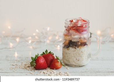 Overnight oats with strawberry on wooden table. Easy breakfast recipe with cereal and fresh berries and fruits