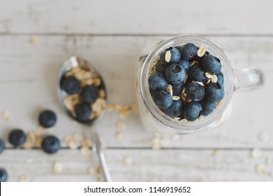 Overnight oats with whole grain cereal and blueberry and spoon with uncooked oatmeal and fresh berries on wooden table, top view. Breakfast meal