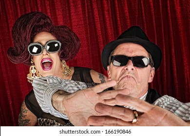 Over-protective man in hat with surprised drag queen
