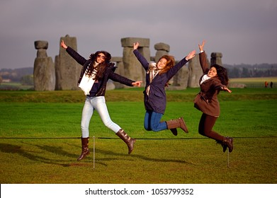 Overseas tourists, Stonehenge, England 2017. Tourists jump while posing for a photograph at Stonehenge one of the most famous landmarks and tourist destinations in the U.K