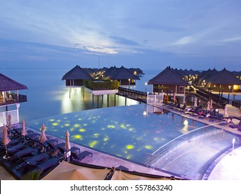 Overseeing the Malacca Strait with a colorful night view at Infinite pool of Avani Sepang Goldcoast Resort, Malaysia.