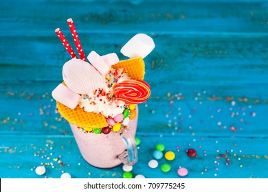 Overshake.  Pink strawberry freakshake with sweets on blue background. Selective focus.