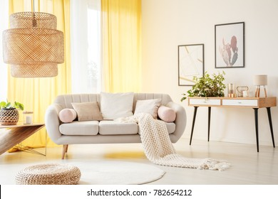 Oversize lamp in light living room with yellow drapes, beige sofa and knit blanket