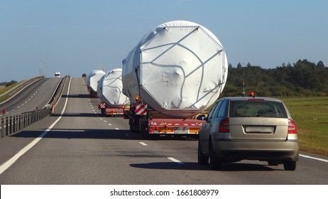Oversize trucks convoy with escort car driving on suburban highway road at Sunny summer day, oversized logistisc business