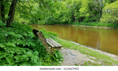 Over-sized weathered wooden bench set in a shady spot with foliage overlooking a river in the upper Midwest with trees & vegetation in the distance. Captured on a sunny afternoon. Spring/ Summer, 2017