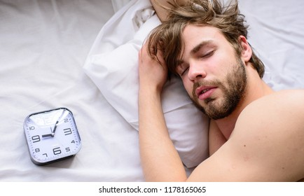 Oversleep problem. Man unshaven sleepy face lay pillow alarm clock top view. Guy sleep missed alarm clock ringing. Manage proper regime tips. Toughest part of morning simply getting out of bed.