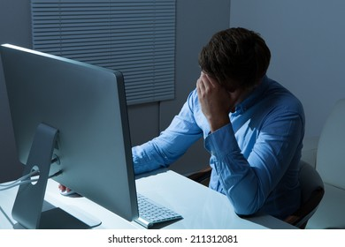Overstressed businessman leaning at computer desk in office