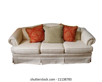 An overstuffed sofa covered in off-white fabric with two paisley pillows and one herringbone pillow isolated on white.