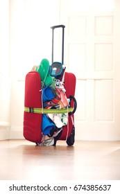 Overstuffed suitcase in hallway