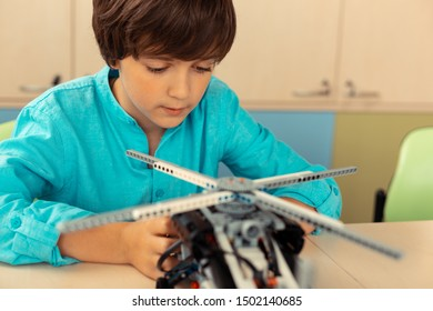 Overthinking ideas. Serious schoolboy sitting in the classroom working on helicopter model made of construction set.