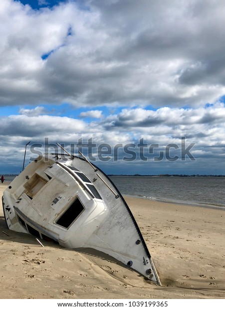 Overturned boat washed ashore by strong storm is buried in sand on a beach with dramatic cloudy sky in the  background in Plumb Beach, Brooklyn, New York