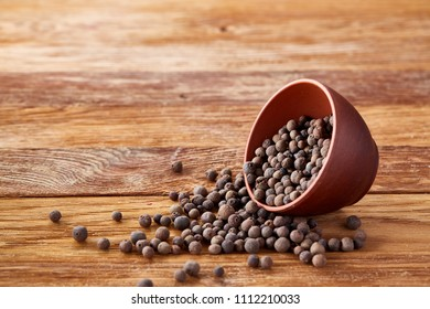Overturned clay bowl with dried allspice berries on rustic wooden background, close-up, macro, selective focus.