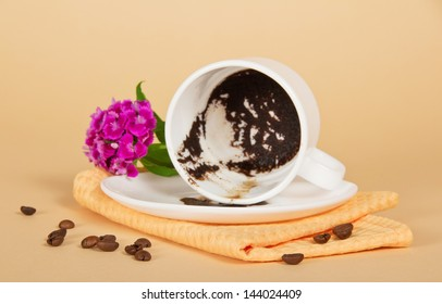 The overturned cup, coffee grains, a bright carnation and a napkin on the beige