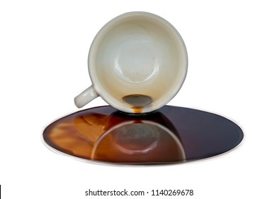 Overturned cup of coffee with coffee puddle