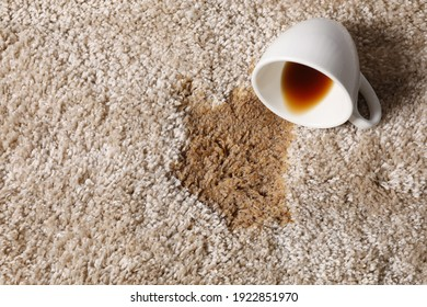 Overturned cup and spilled coffee on beige carpet, above view. Space for text