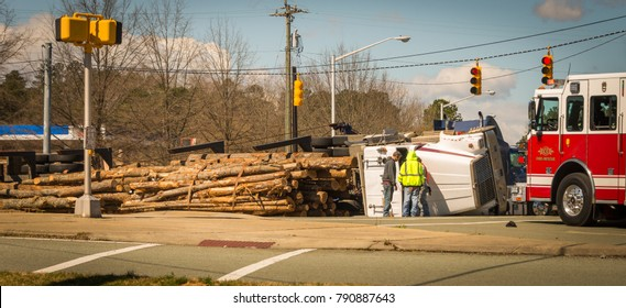 Overturned logging truck with work men and fire engine