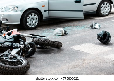 Overturned motorcycle and helmet on the road after a collision with a car