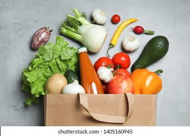 Overturned paper bag with bottle of juice, vegetables and fruits on grey background, flat lay