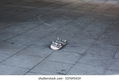 Overturned upside down alone skateboard on playground