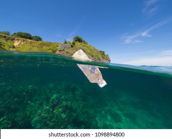 Over/under split photo of a plastic bottle floating on the surface of a coral lagoon