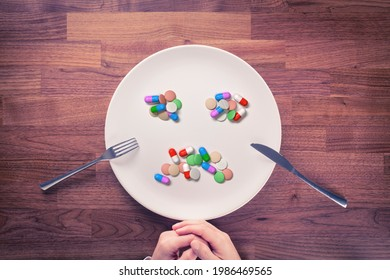 Overuse of drugs or pills, dietary supplements and vitamins concept. Person prepared for eating with cutlery and plate full of drugs or vitamins in shape of sad emoticon.