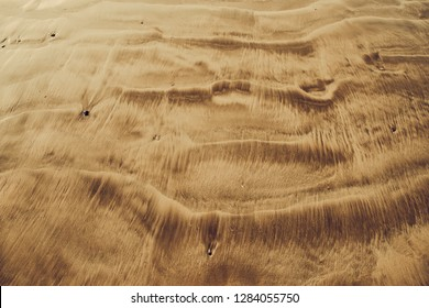 Overview aerial shot of the volcanic sand. Indonesia. Close-up dune waves with the sepia tone. Ideal background, texture for the different kinds of the collages, illustrations and digital media.
