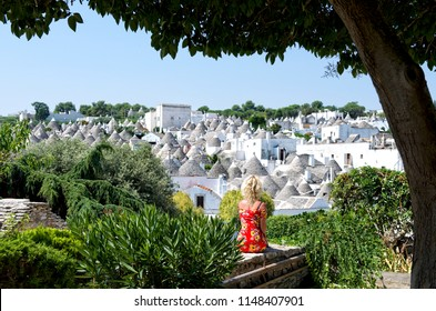 An overview of the Alberobello -a small town in southern Italy famous for its unique trullo/trulli buildings which have been designated as UNESCO World Heritage. Woman sitting and looking to the city