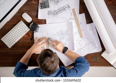 Vue d'ensemble de l'ingénieur chargé avec règle et crayon assis à côté de la table et ligne de dessin sur croquis de construction architecturale