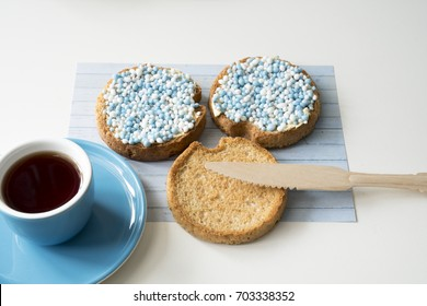 overview celebration the birth of a sun with dutch crisp bakes with blue sugared aniseed balls, muisjes, cup of coffee against white background