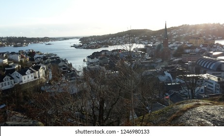 An overview of the city arendal in Norway. You can see the sea and a monument of a clock tower on a clear day.