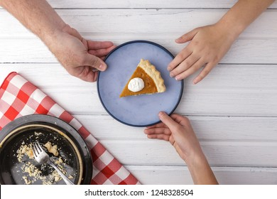 An overview of hands reaching for the last piece of pumpkin pie.