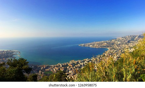 Overview of Jounieh Bay,  with continuous urbanism between Jounieh and Tabarja on mediterranean shore in Lebanon, with two paragliders flying about, with the blue of the sea in background