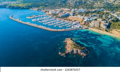 Overview of large marina with yachts, in Puerto Portals Mallorca. Including Turquoise water, rocky landscape, yachts, beach and coastline town.