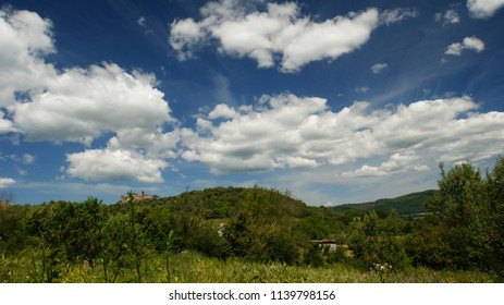 overview of the Lazio countryside, with the Bracciano castle on the background with blue sky and clouds