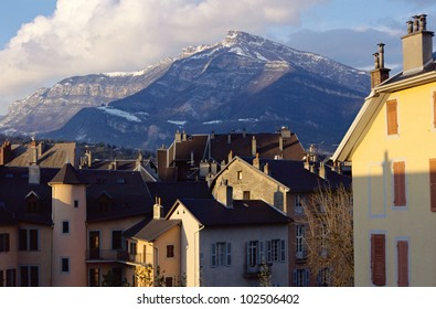 Overview of old town's roofs and Nivolet cross mountain in Chambery, Savoy, France at sunset