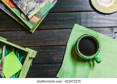 Overview on cup of coffe on green fabric napkin on the black wood background. Shallow focus. Part of wooden box with green stationary and stack of books.