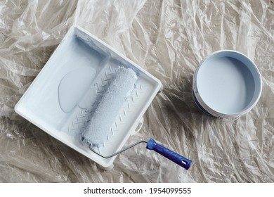 Overview of of paintroller, white plastic bucket and square container with paint on the floor of room of new house or flat during home renovation
