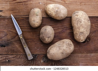 An overview photograph of whole potatoes on a pearing knife.