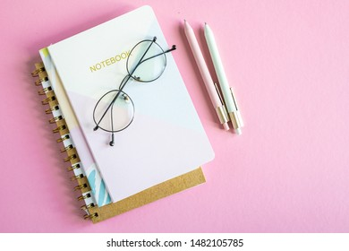 Overview of pink table with stack of notebooks, eyeglasses and two pens