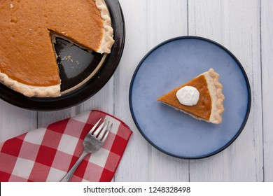 An overview of a plate of pumpkin pie with a napkin and fork.