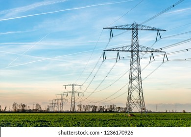 Overview of power pylons and high voltage lines in a long row in a rural landscape. The photo was taken in De Biesbosch, a nature area near the village of Werkendam,  North Brabant, Netherlands
