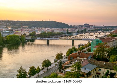 Overview of Prague from Vysehrad, yellow and pink sunset sky, railway bridge over the river Moldau, Czech Republic, Europe