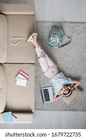 Panorama de un adolescente relajado con ropa informal y auriculares escuchando música mientras se relaja en el suelo en un sofá en casa