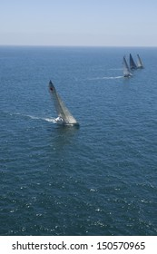 Overview of sailboats racing in the blue and calm ocean against sky