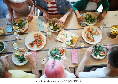 Overview of tasty food on served wooden table and several young friendly people sitting around and having lunch